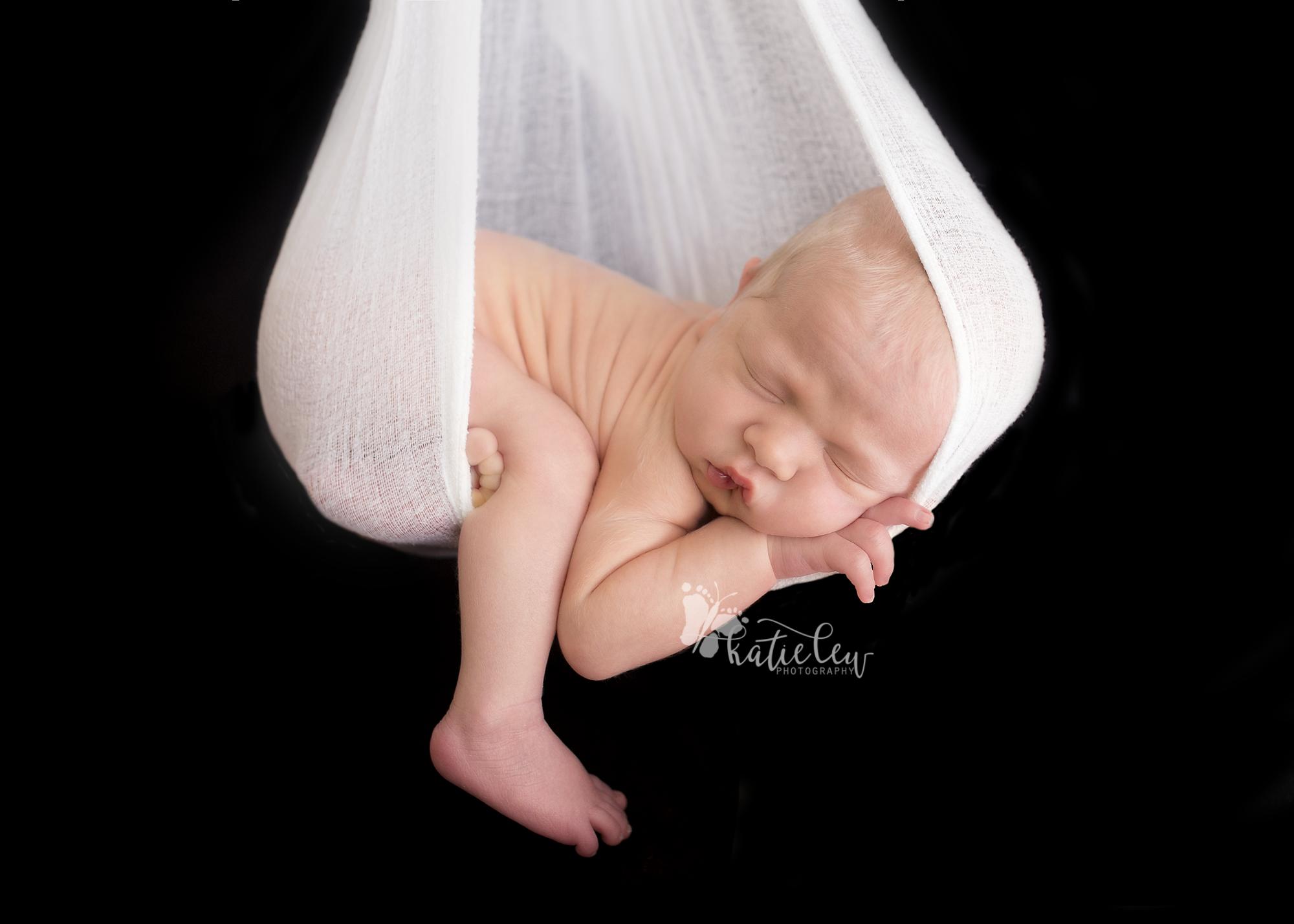 newborn sleeping in a wrap hammock