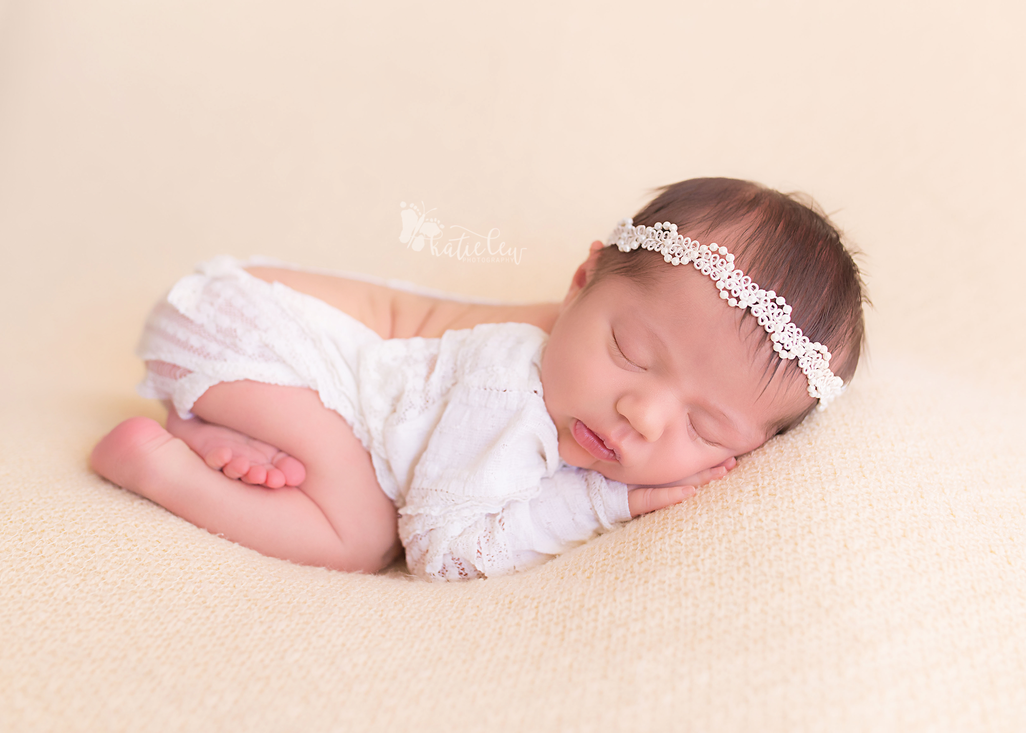 Newborn girl wearing white lace romper
