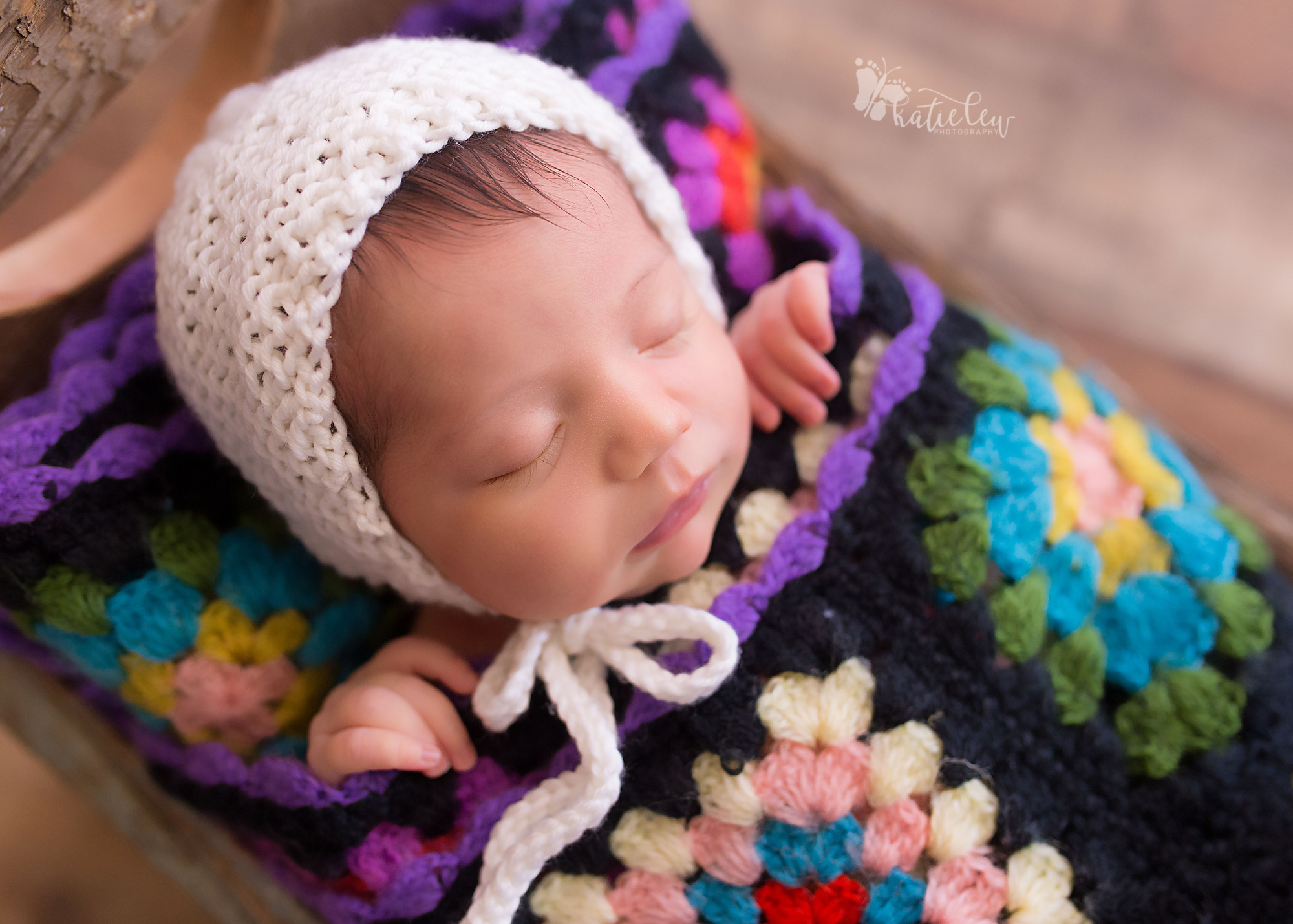 Baby tucked in a bed wrapped in a crochet quilt