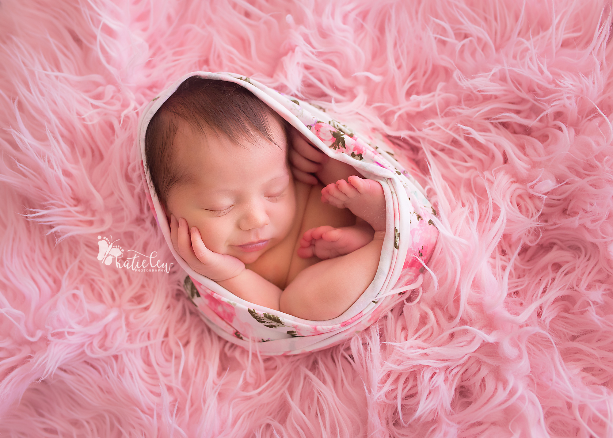 baby girl smiling and nestled in pink fur