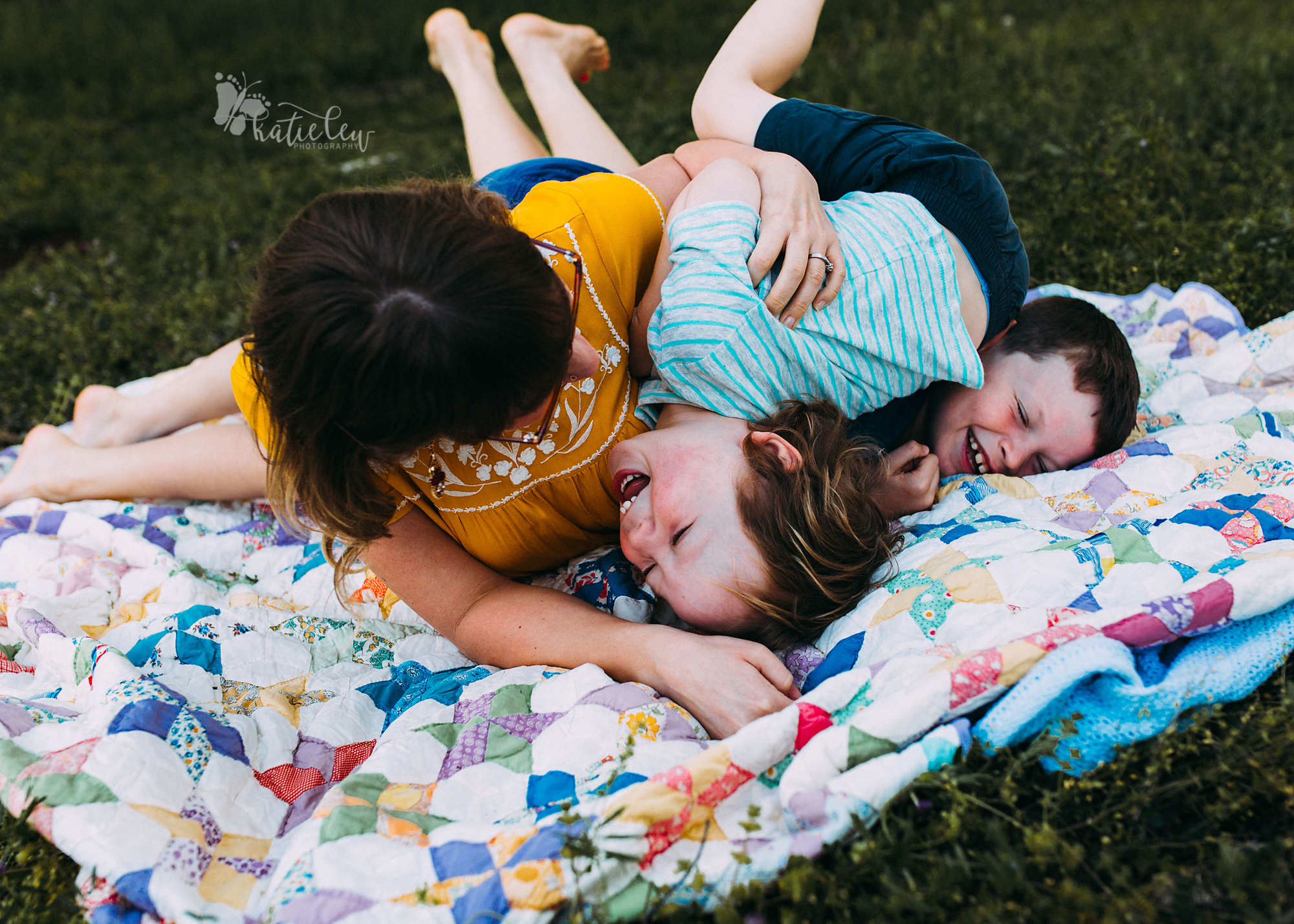 a mom on a quilt with her sons playing tickle