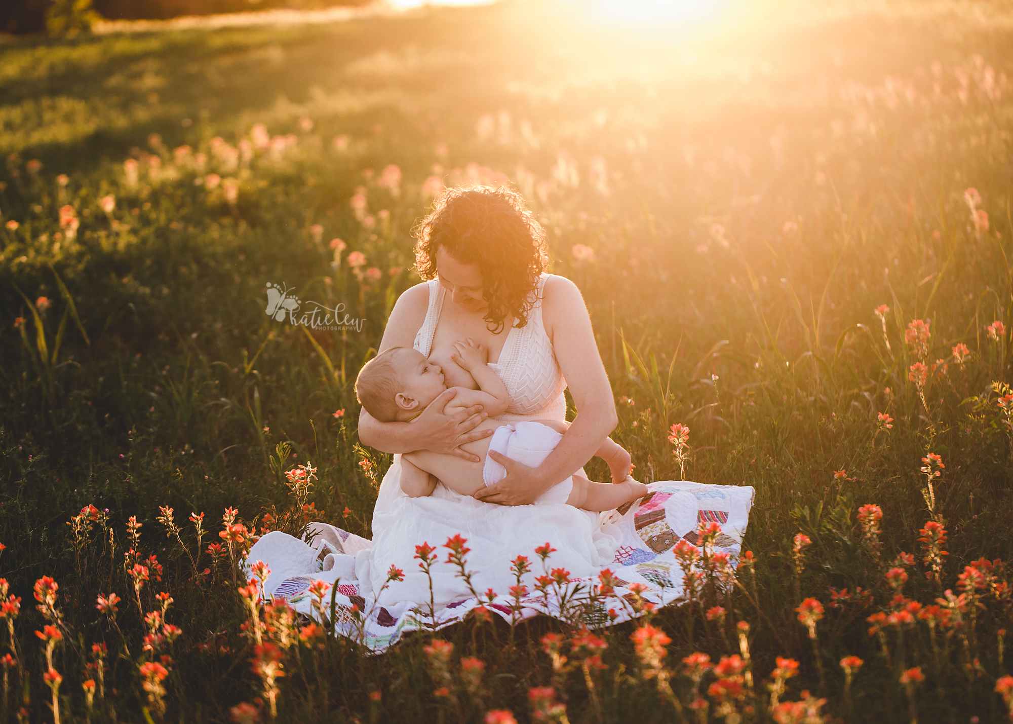a mother sits on a quilt in an open field and breastfeeds her son