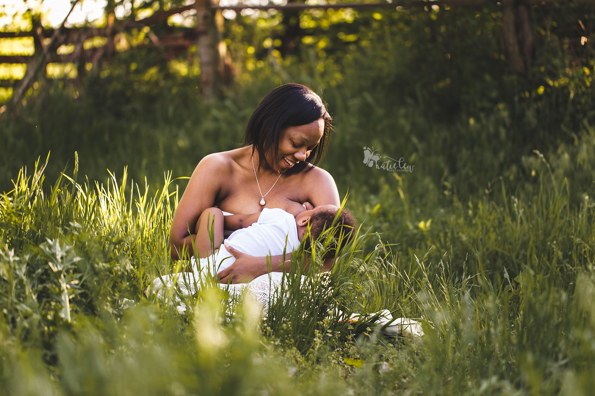 a mother sitting in the grass breastfeeding her son
