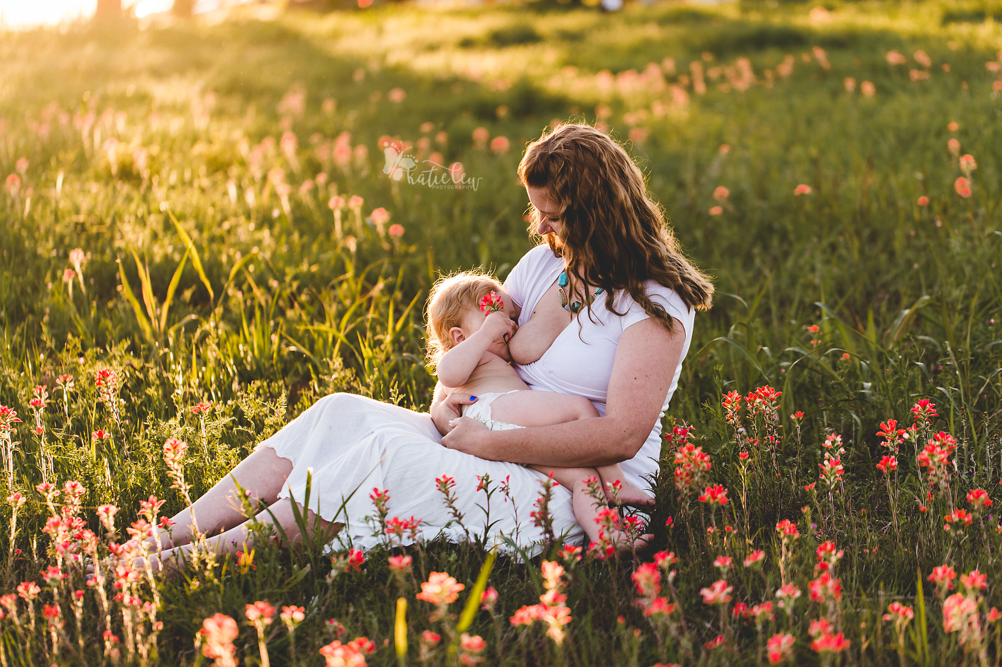 a little boy holds an indian paintbrush while breastfeeding