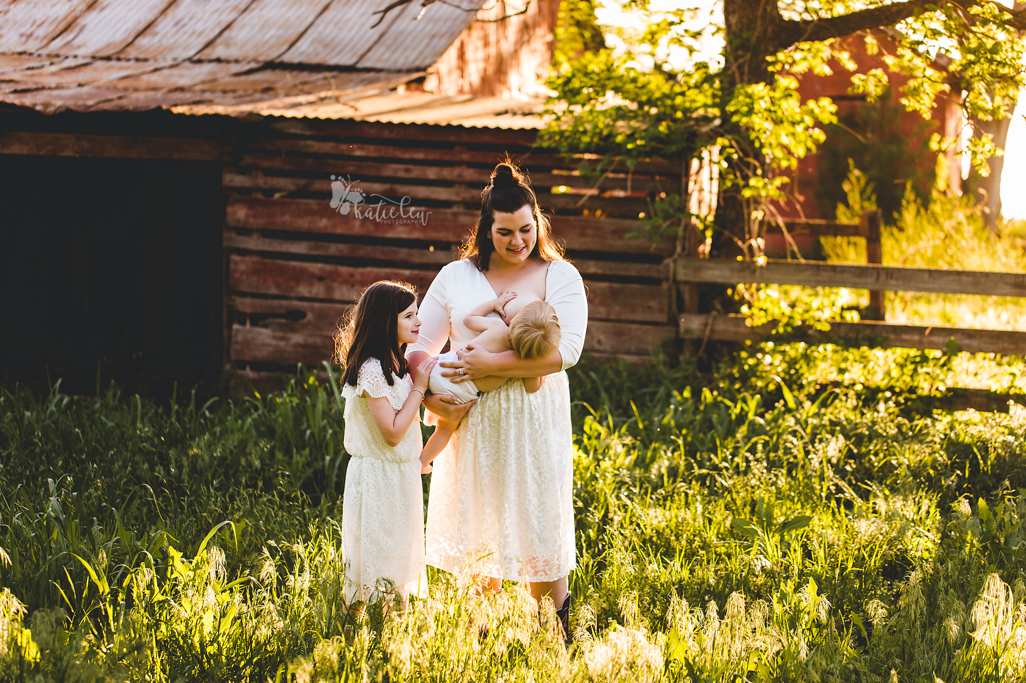 a mother and her daughter look on lovingly as her youngest baby breastfeeds
