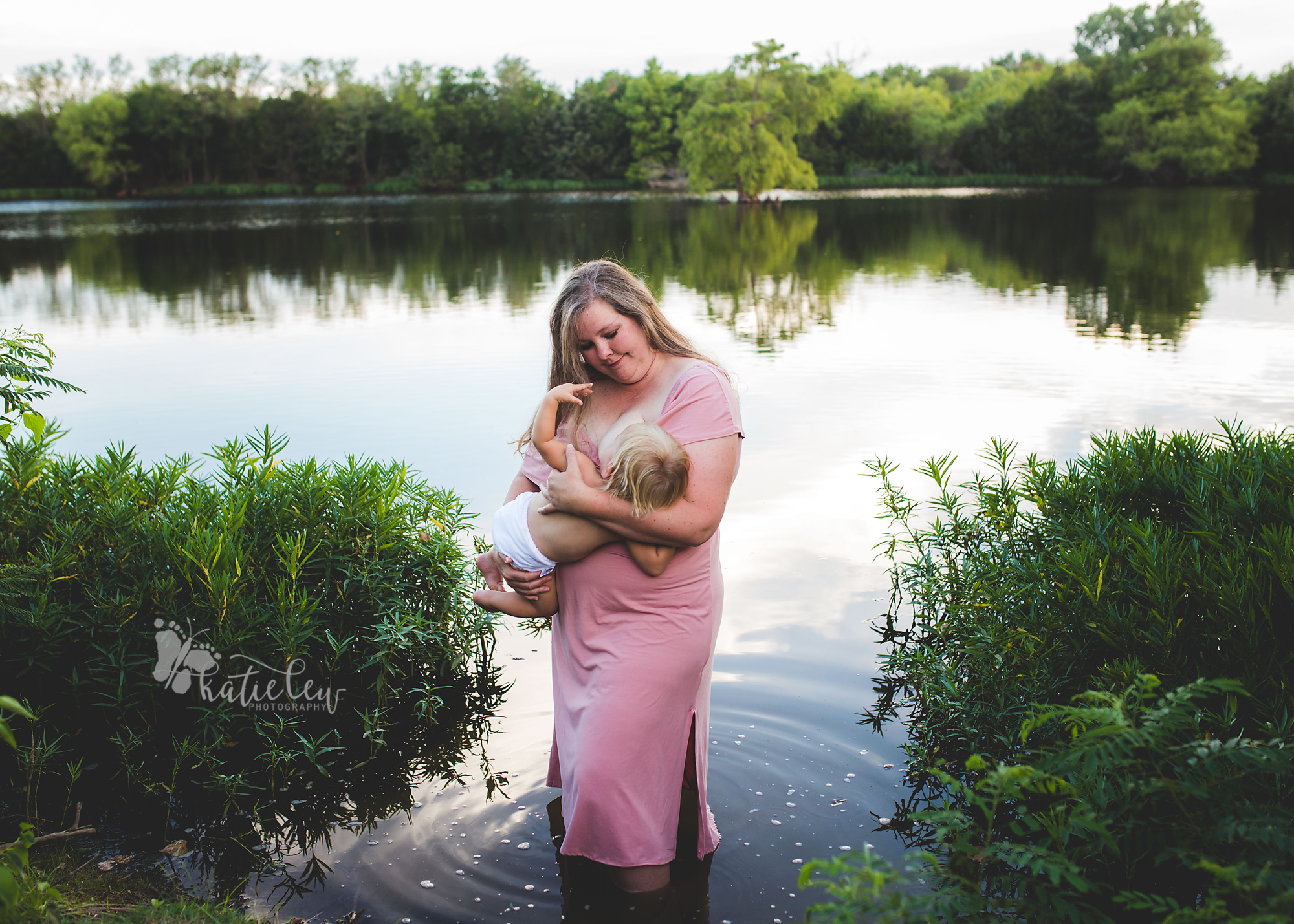 beautiful mother in pink dress breastfeeding her baby girl