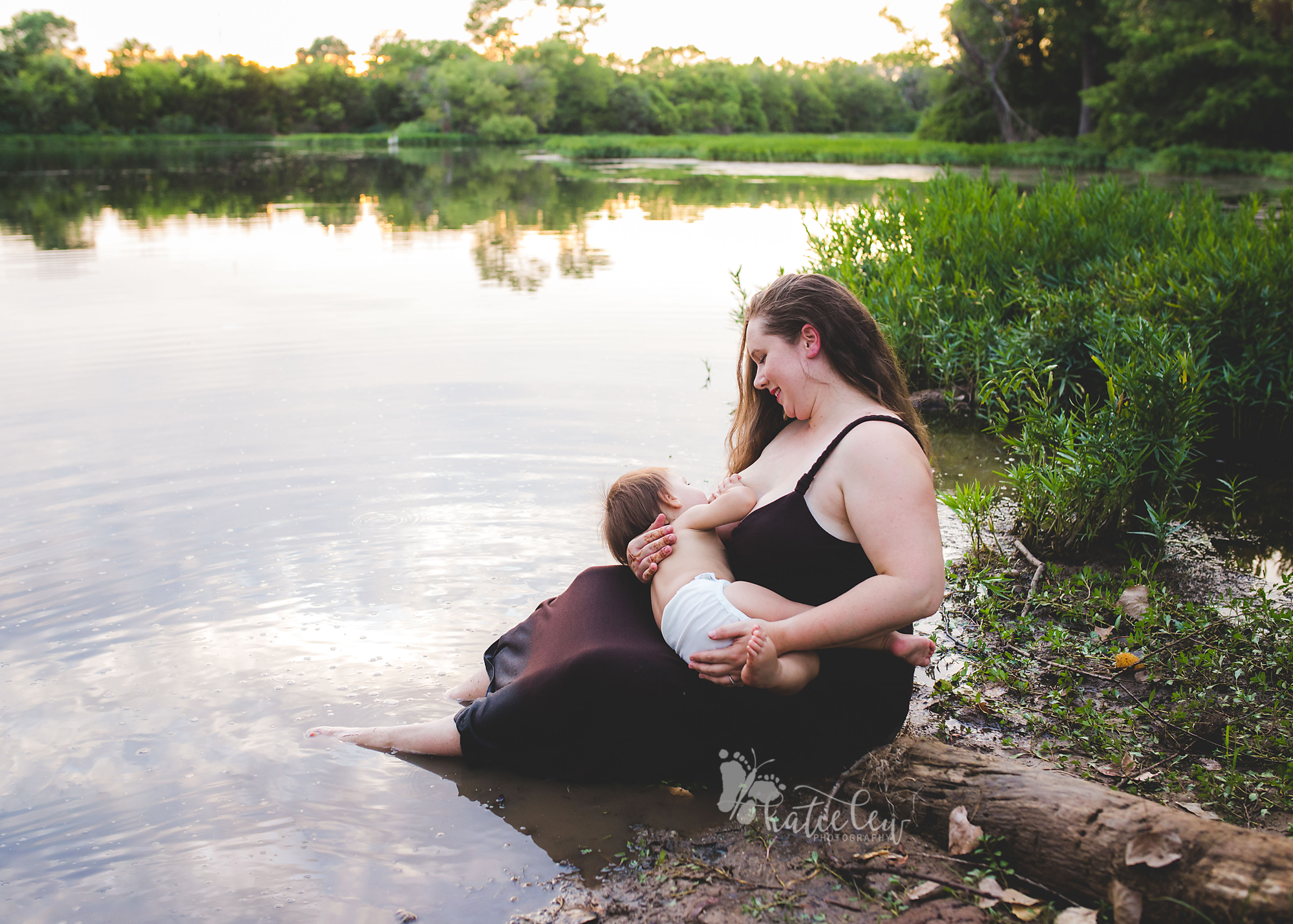 woman in a brown dress breastfeeding her son in water