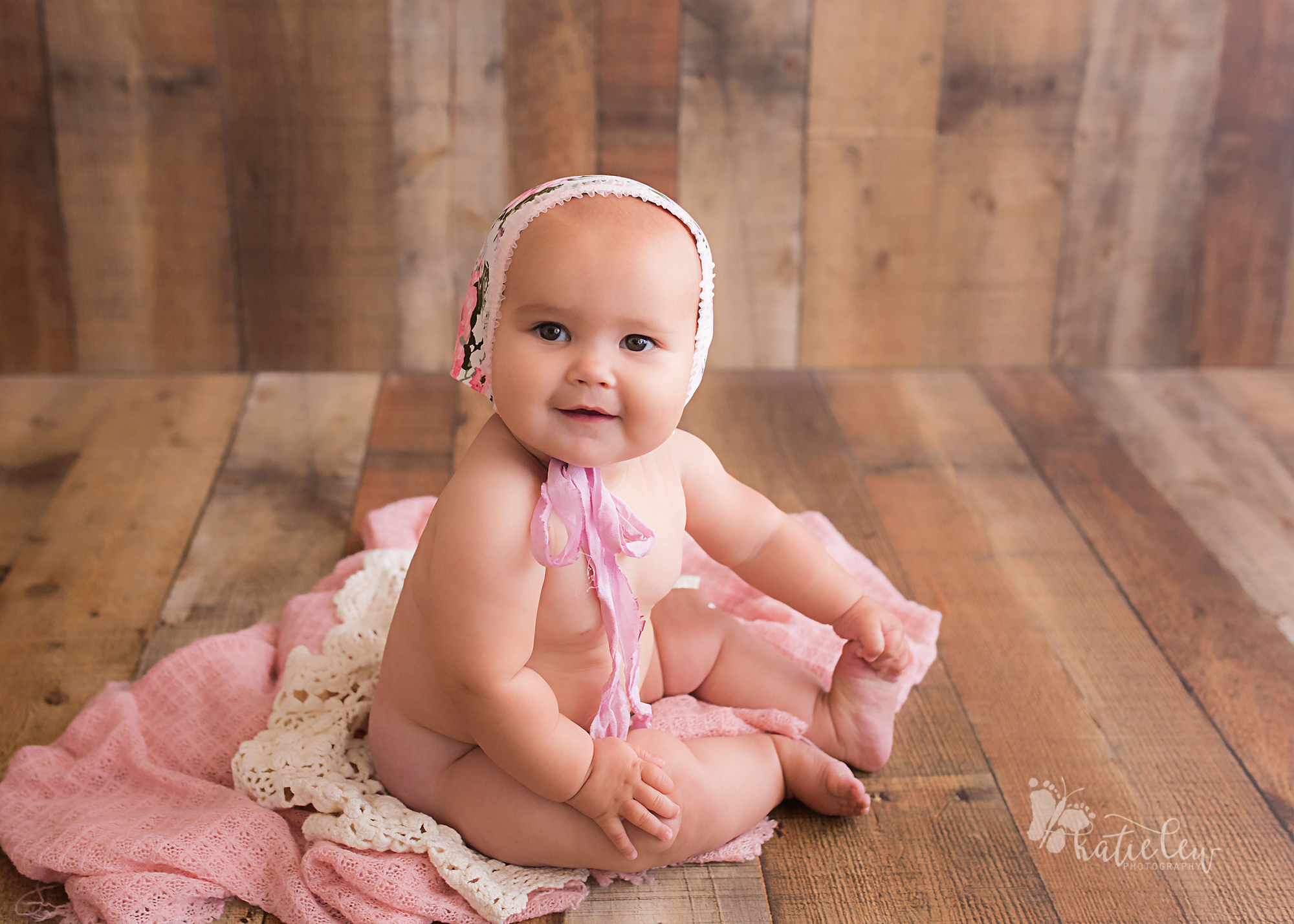 6 month baby naked except for a cute floral bonnet