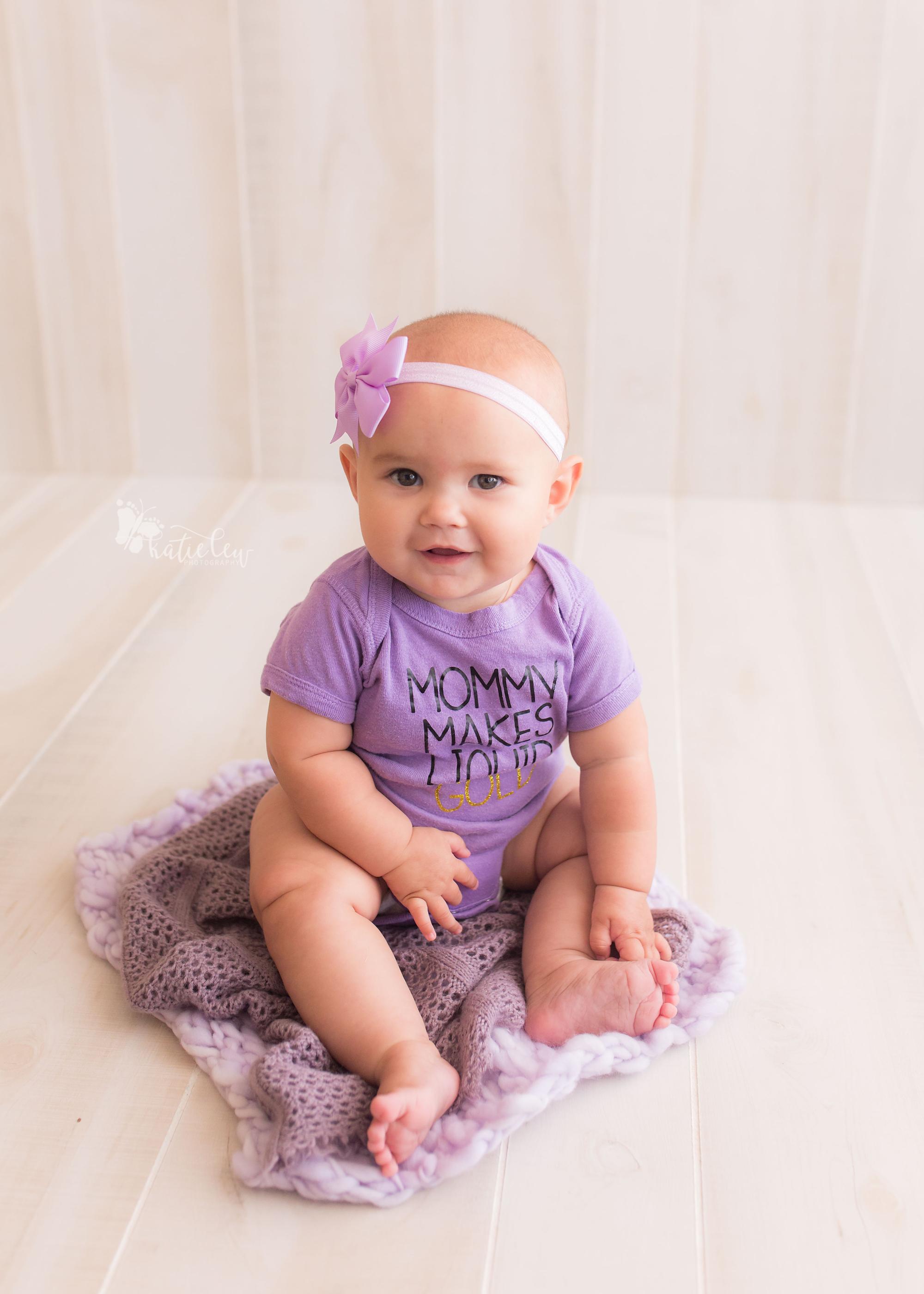 "Little baby girl wearing purple ""mom makes liquid gold"" onesie"