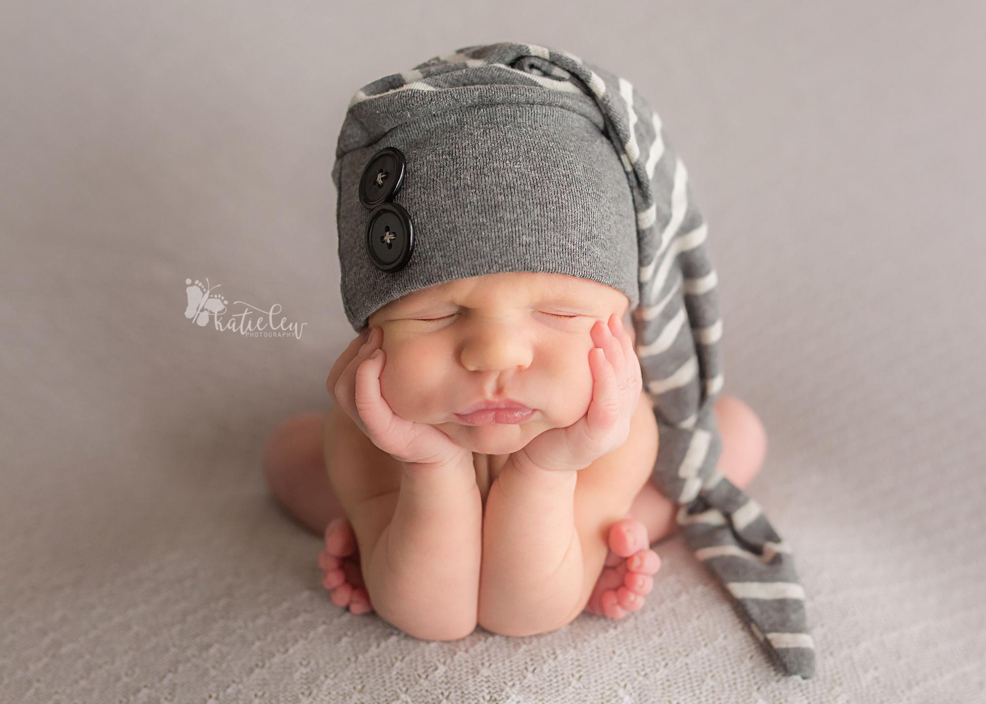 newborn baby boy wearing a striped hat