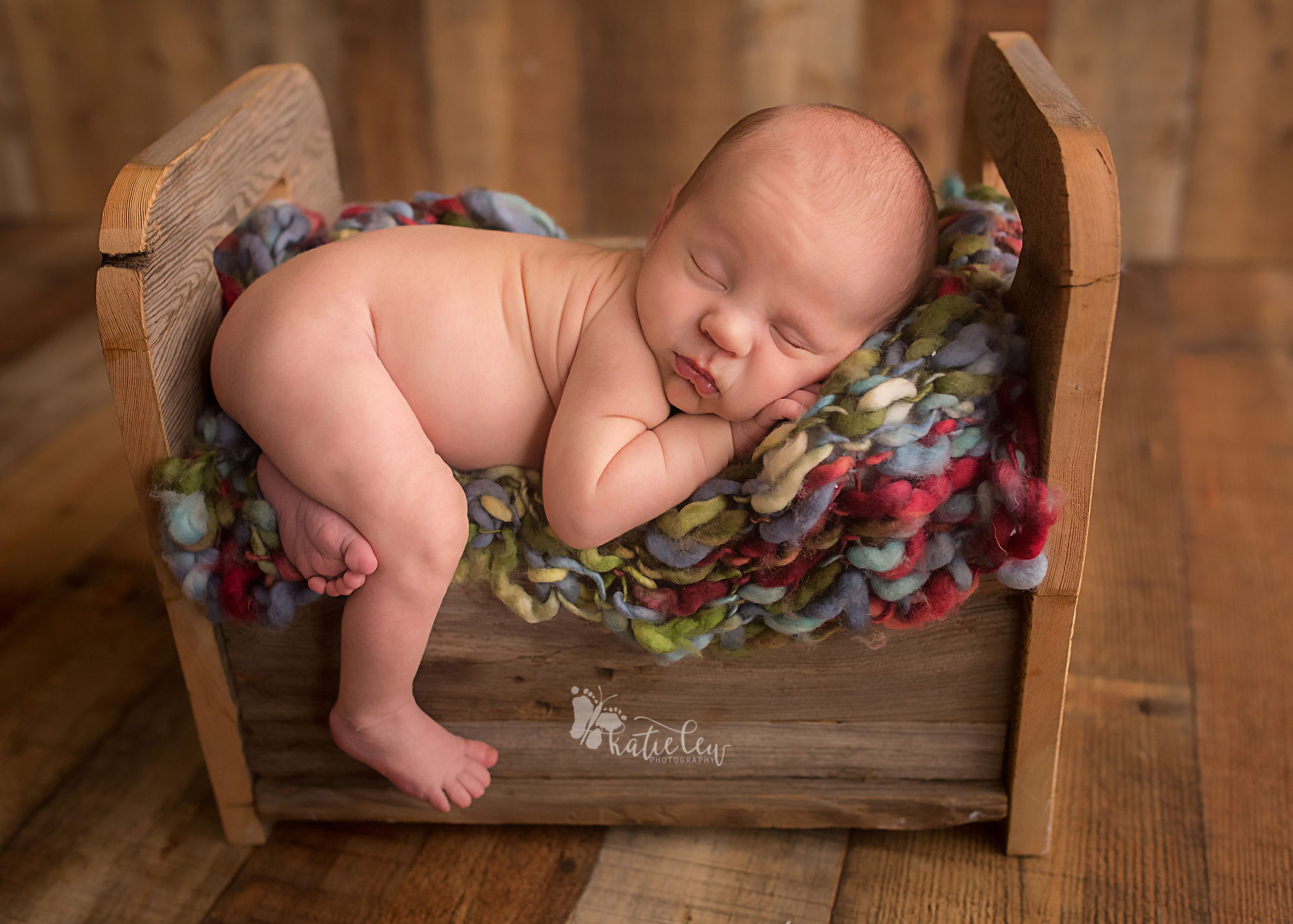 tiny baby bed with a newborn baby boy in it.