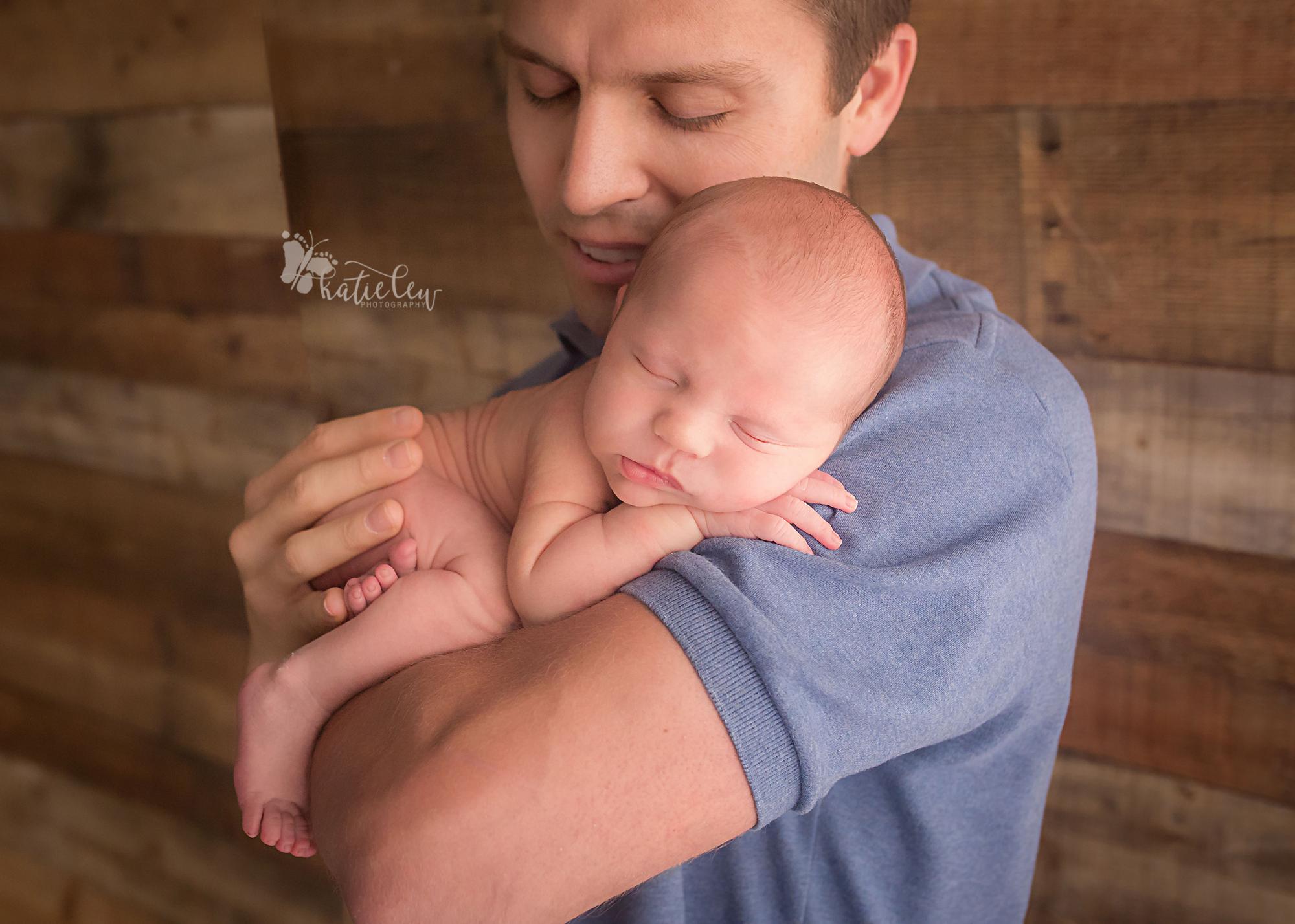 newborn snuggled up on daddy