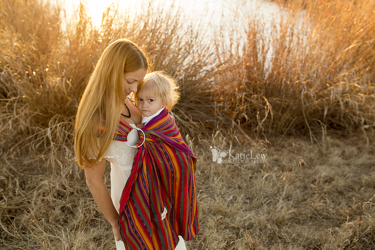 young mother wearing her son in a beautiful ring sling