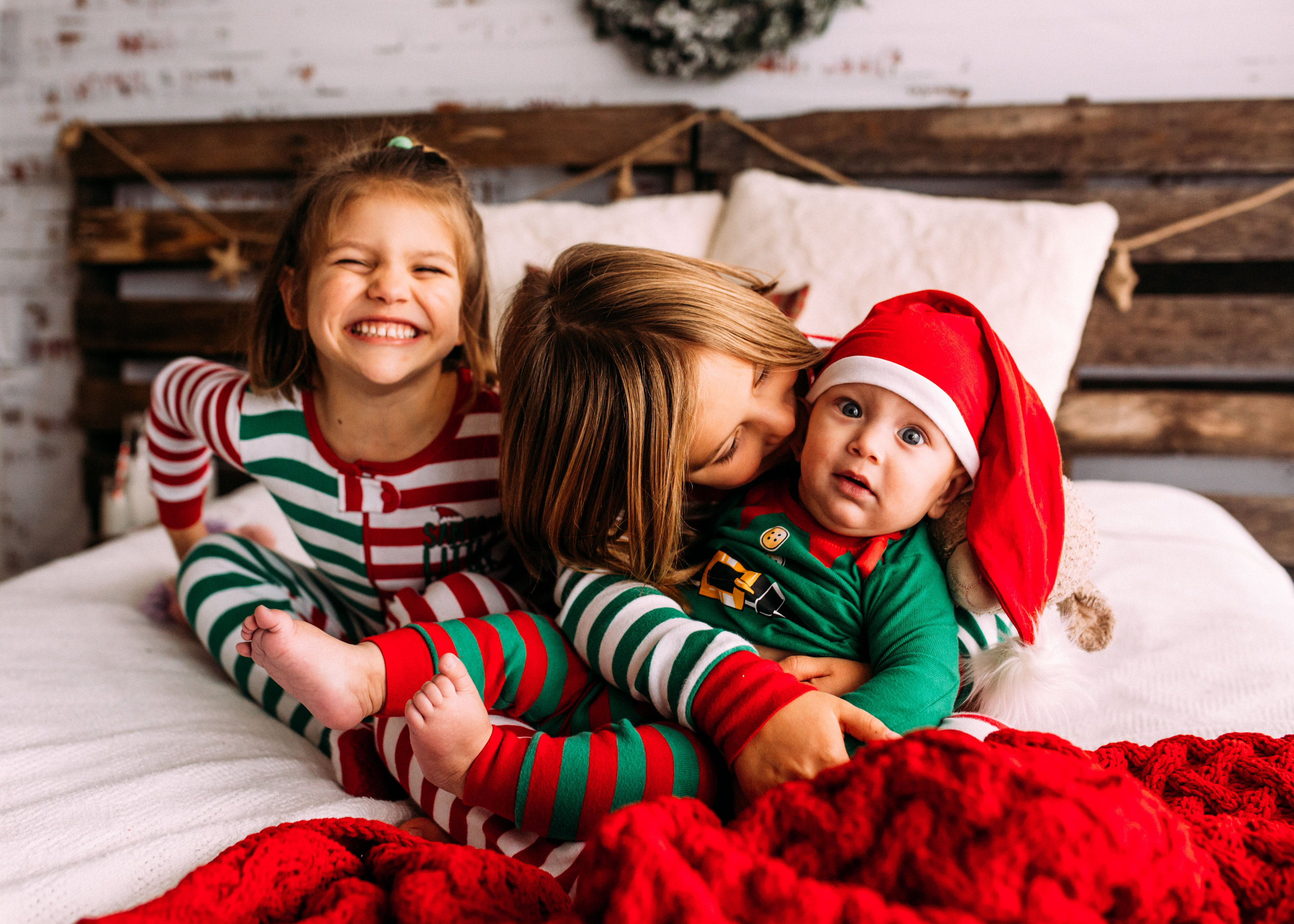 children in Christmas PJ's snuggling on bed