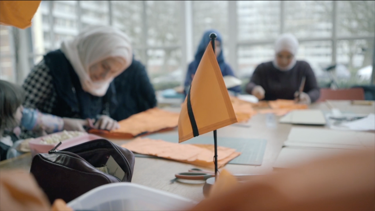 The flag is now a primary source of income for newcomer refugees. Making flags out of real life vests, is a project in partnership with Makers Unite.