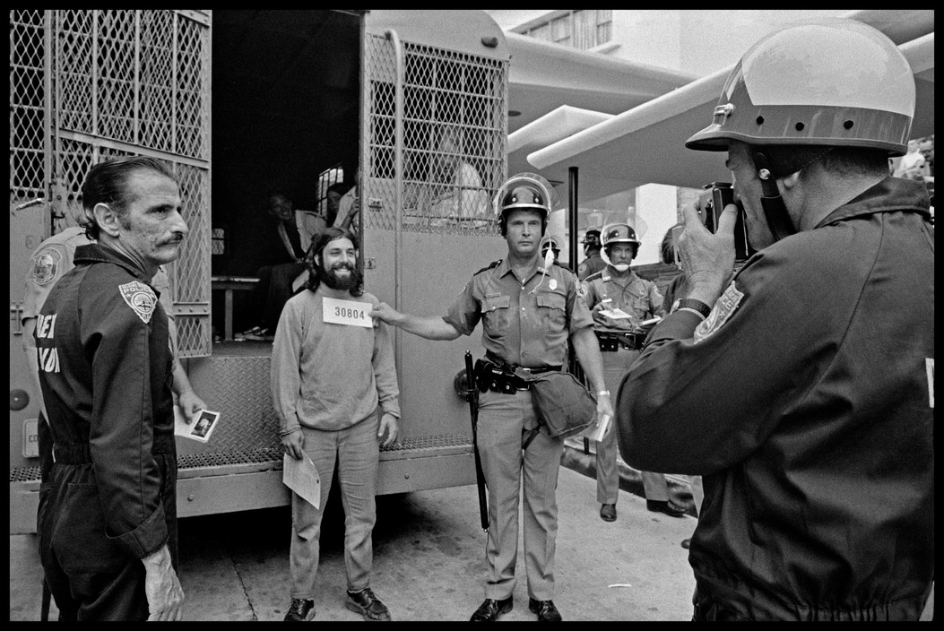 An anti-Vietnam war activist, under arrest, smiles while being photographed by the police. Photographed by Abbas/Magnum.