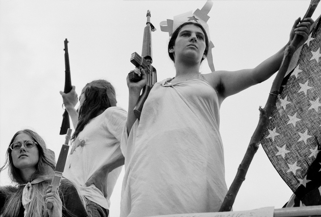 At a women's liberation rally at the Republican convention, a protestor dressed as the Statue of Liberty holding the American flag and a mock M16 gun. Photographed by Abbas/Magnum.