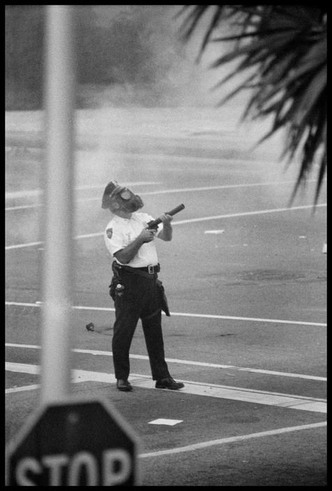 A gas mask policeman firing an anti-riot gas canister at anti Vietnam war activists. Photographed by Abbas/Magnum.