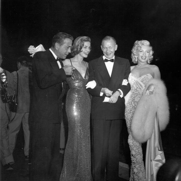 Wearing a Norman Norell sequin 'Mermaid' dress, Lauren Bacall sparkles next to Humphrey Bogart and Marilyn Monroe at the premiere of  How To Marry A Millionaire  on November 4, 1953 in Los Angeles.