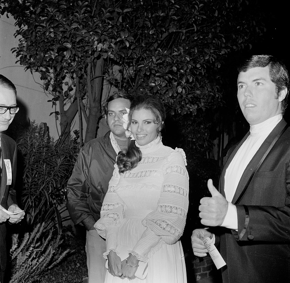 In a high-necked white dress and flower behind her ear, Raquel Welch looks girlish and romantic while attending an event in LA with husband Patrick Curtis in 1967.