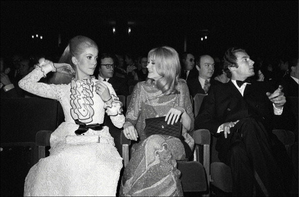 Sisters Catherine Deneuve (in white lace and ruffles) and Françoise Dorléac (in slinky lurex) at the premiere of  Les Demoiselles de Rochefort  in Paris on March 7, 1967.