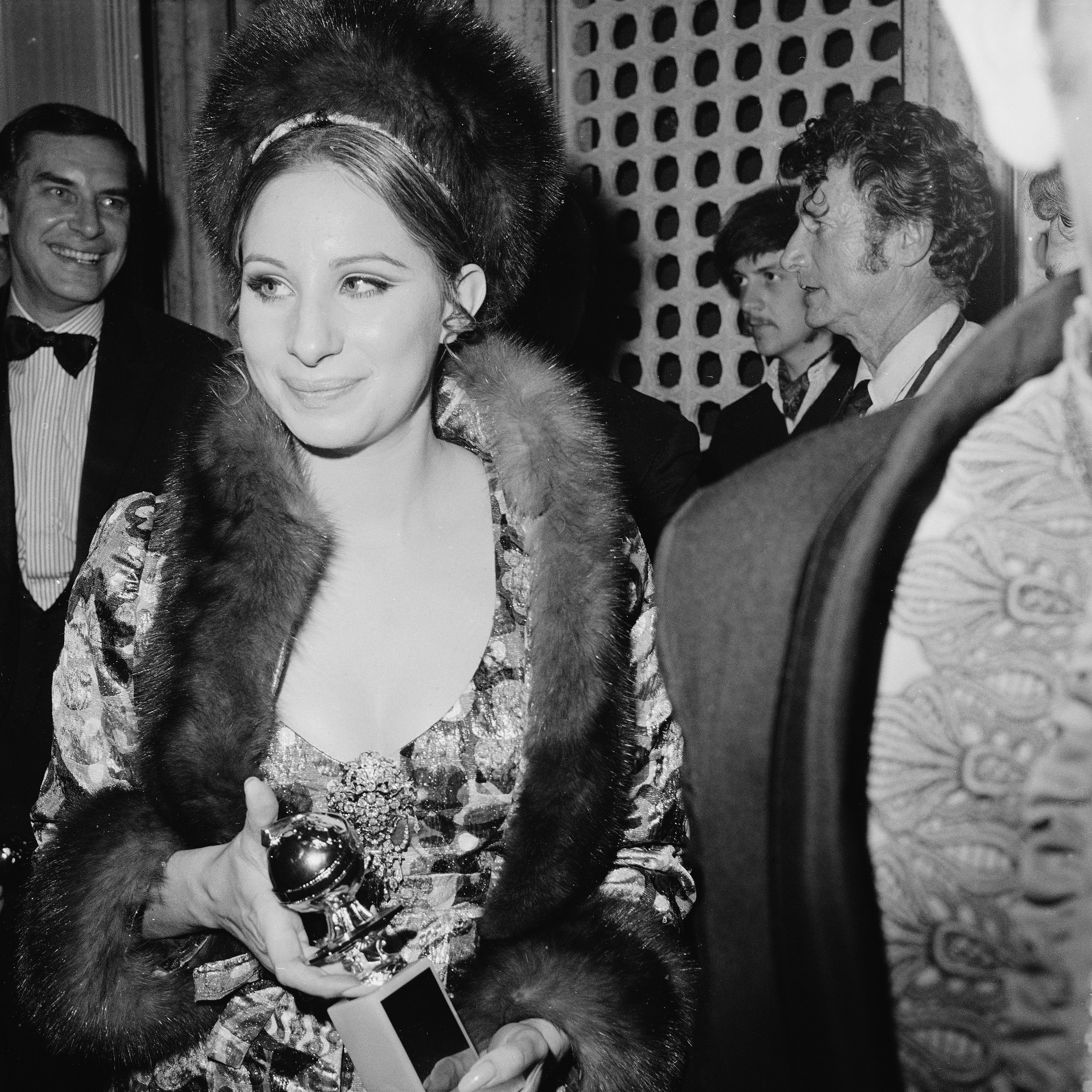"Barbra Streisand—all shimmering brocade and fur—carrying her award for ""Best Performance by an Actress in a Motion Picture – Comedy or Musical"" during the 26th Annual Golden Globe Awards on February 28, 1969."