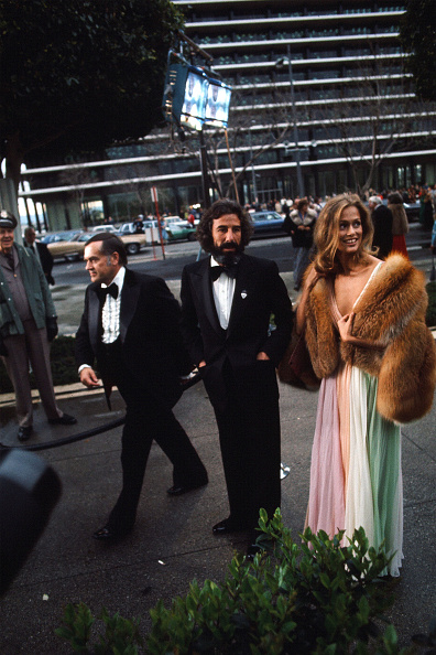 Wearing candy-colored Halston, Lauren Hutton walks into the Dorothy Chandler Pavilion for the 47th Academy Awards on the arm of Lou Adler.
