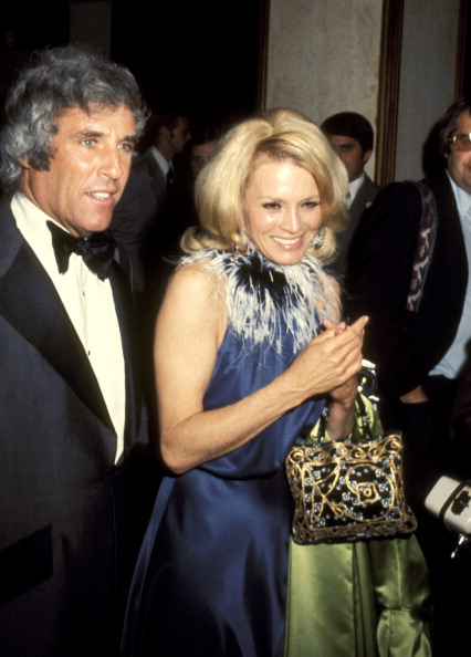 In a simple navy silk dress with feather trim, Angie Dickinson arrives with husband Burt Bacharach to the American Film Institute Salute to William Wyler on March 9, 1976.