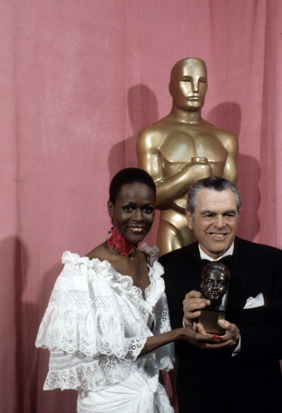 In a riot of white lace with a red flower choker, Cicely Tyson presenting Pandro Berman with his Irving G. Thalberg Memorial Award at the 49th Annual Academy Awards, on March 28, 1977.