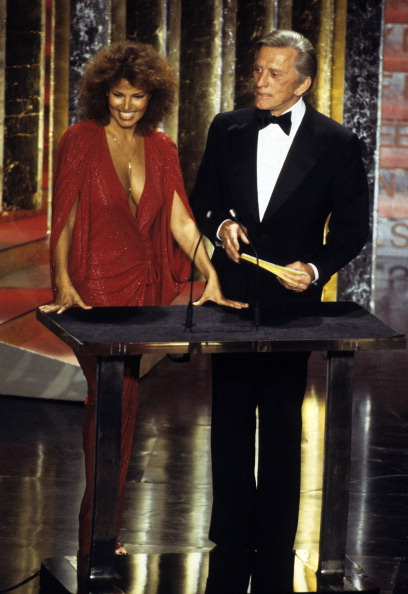 Proving why she is still considered one of the sexiest women ever, Raquel Welch presenting an award alongside Kirk Douglas while wearing a plunging, red lurex draped dress at the 50 th  Academy Awards on April 3, 1978.