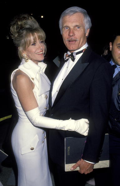Jane Fonda in the best of the early nineties—a sleeveless white double-breasted suit with large gold buttons and matching white opera gloves—at the Academy Awards on March 29, 1993.
