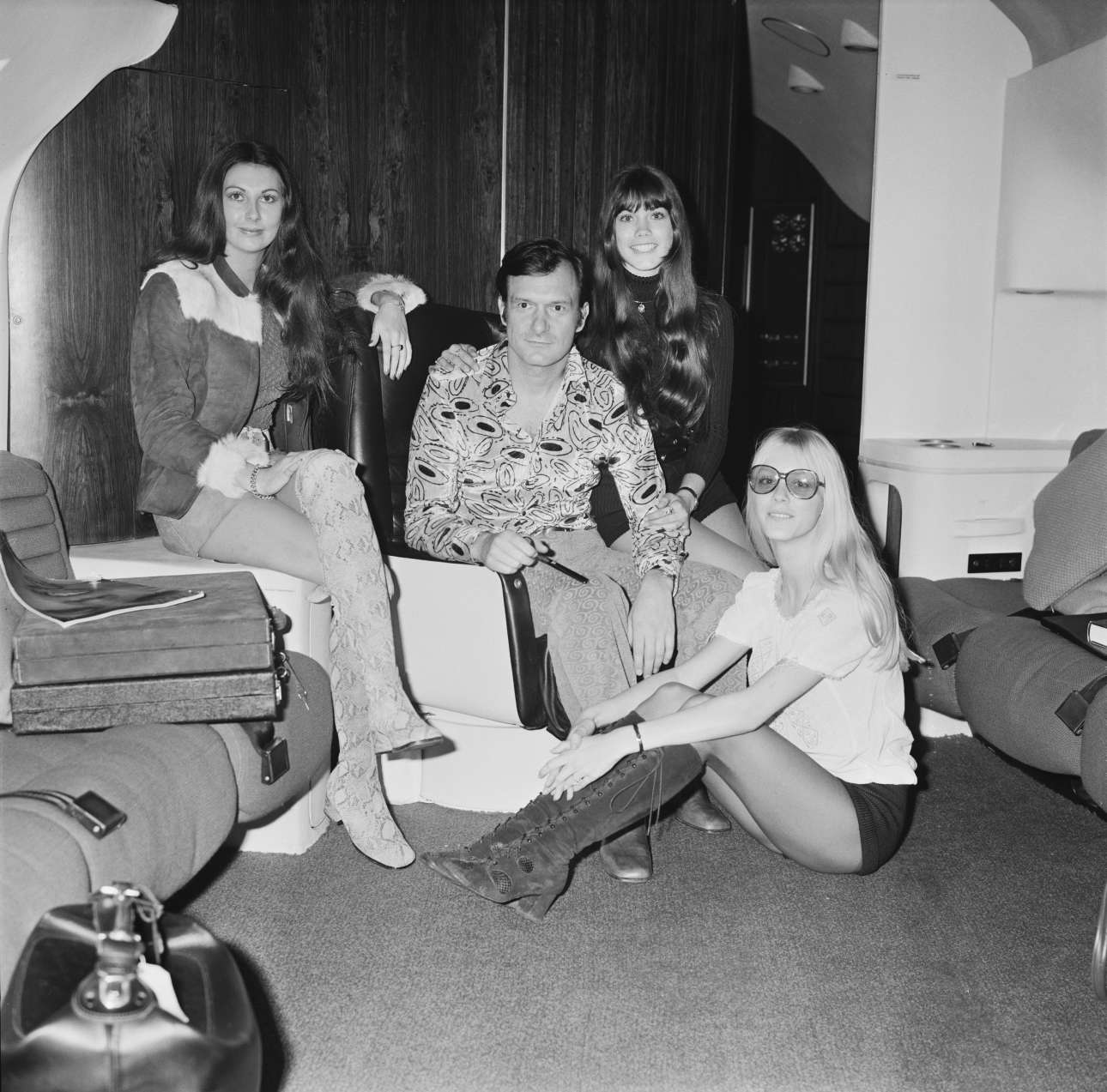 Hefner in his aircraft in London, before flying back to Chicago, 20th February 1971. With him are Playboy models (left to right) Marilyn Cole, Barbi Benton and Connie Kreski.