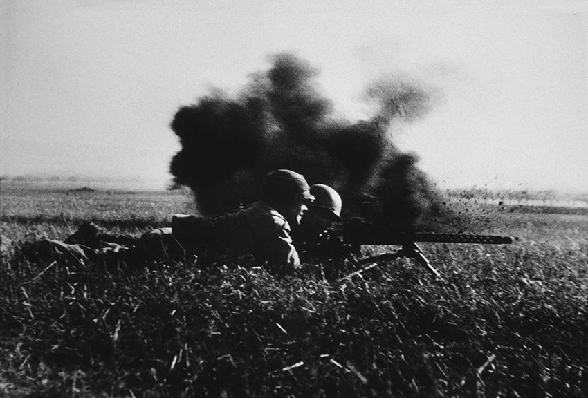 A machine gun team in action just as a German mortar exploded, near Walternienburg, Germany, April, 1945.