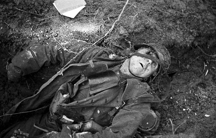 A dead German soldier at a machine gun nest has fallen near a newly opened Christmas card, Hurtgen Forest, Germany, December 20, 1945