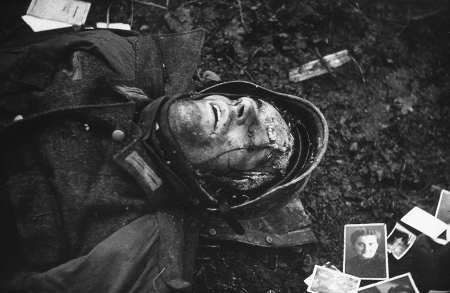 A dead German soldier lies amongst photos of his family, Hurtgen Forest, Germany, January, 1945