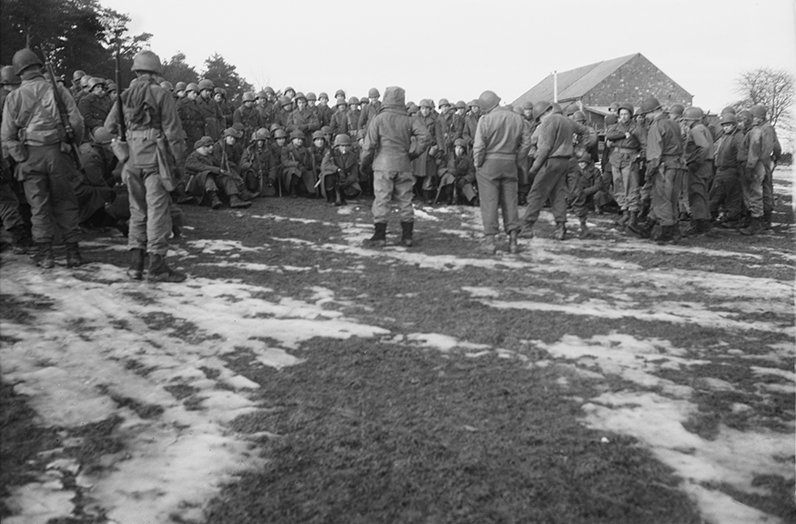 After the Battle of the Bulge, commanders of the 331st Regiment hold an impromptu meeting with their troops to discuss options, near Bastogne, Belgium, January, 1945