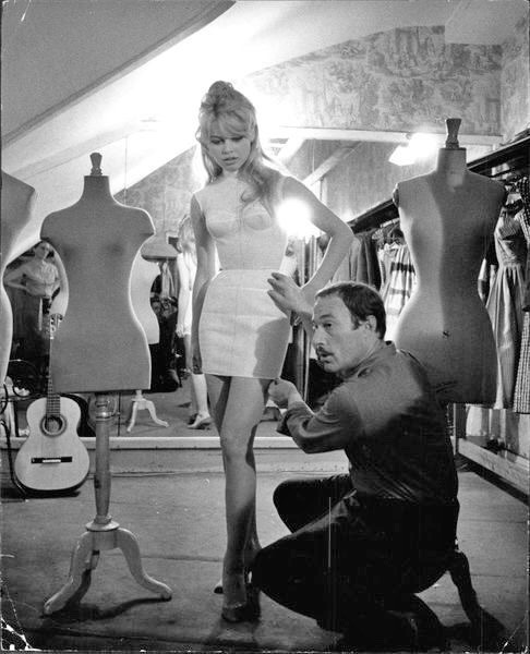 BRIGITTE BARDOT BEING FITTED BY JACQUES ESTEREL, 1958.