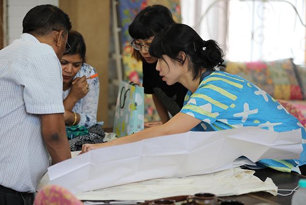 蔡宜穎(藍衣者)與繭裹子夥伴在印度工廠討論產品。圖片來源/繭裹子提供