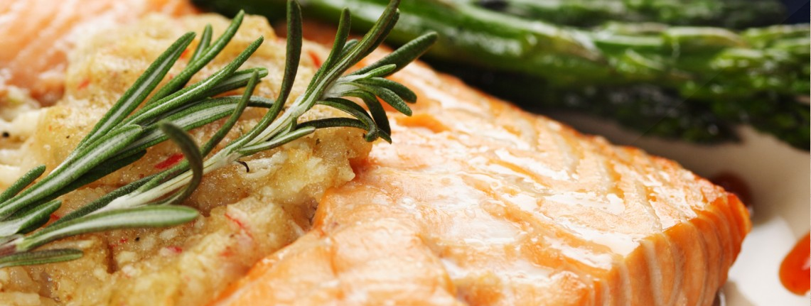 A baked stuffed salmon with asparagus on the side.