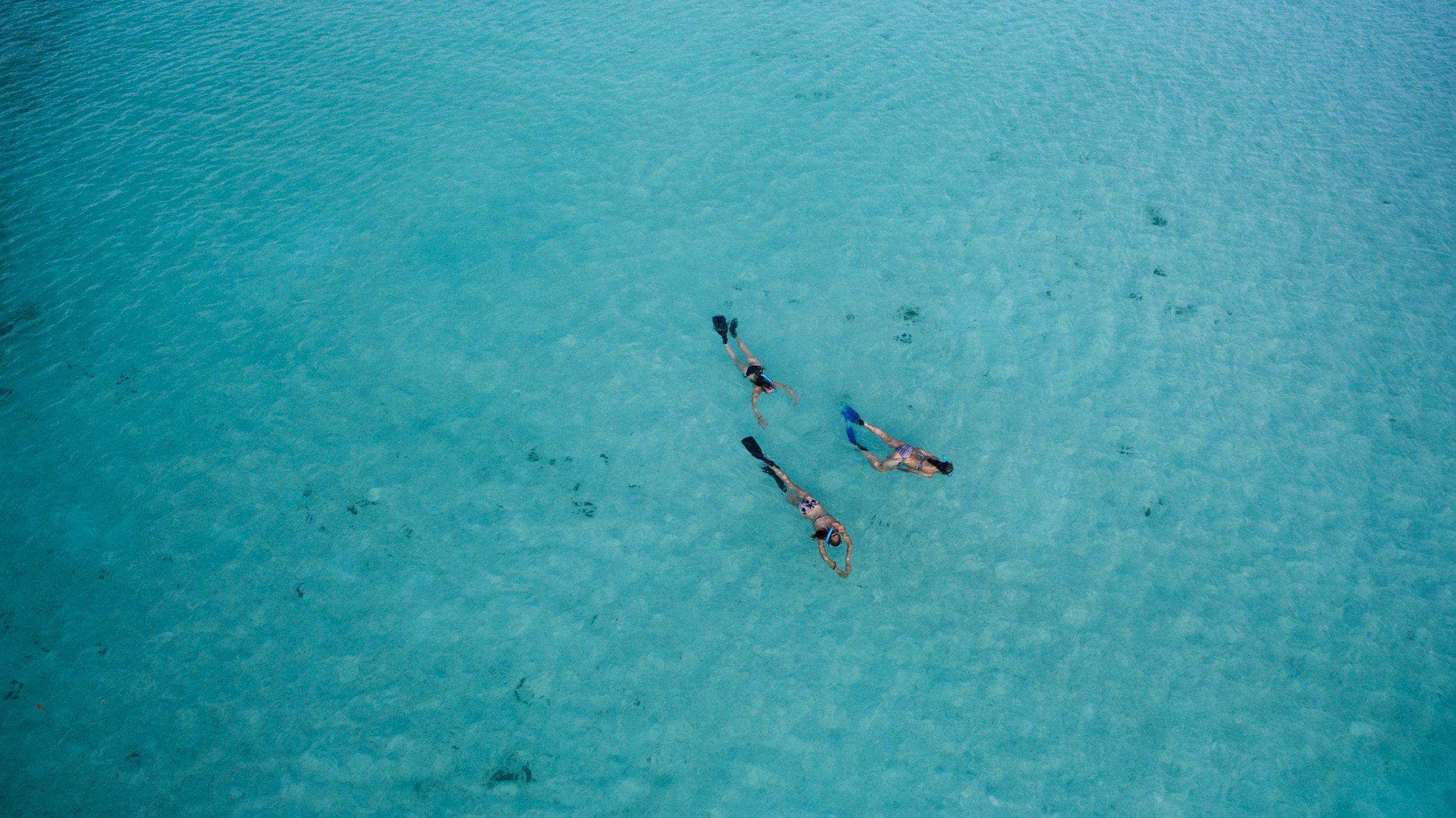 3 women snorkeling turquoise water (1).jpg
