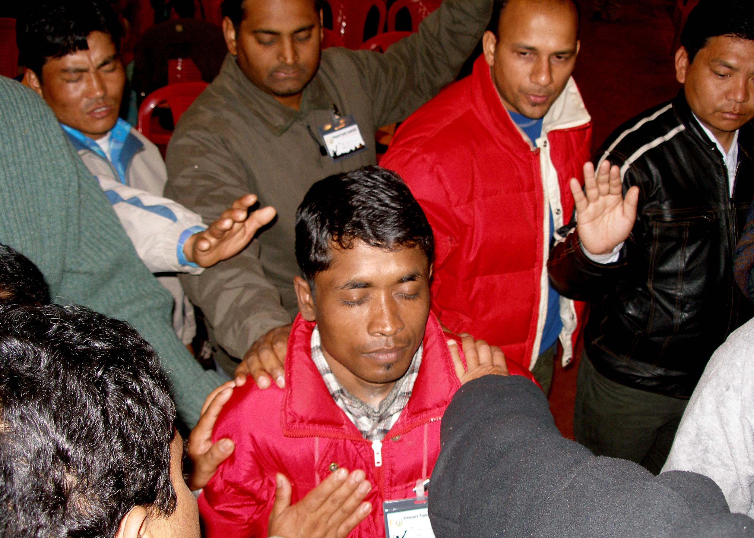 INDIA - Group praying over a man.jpg