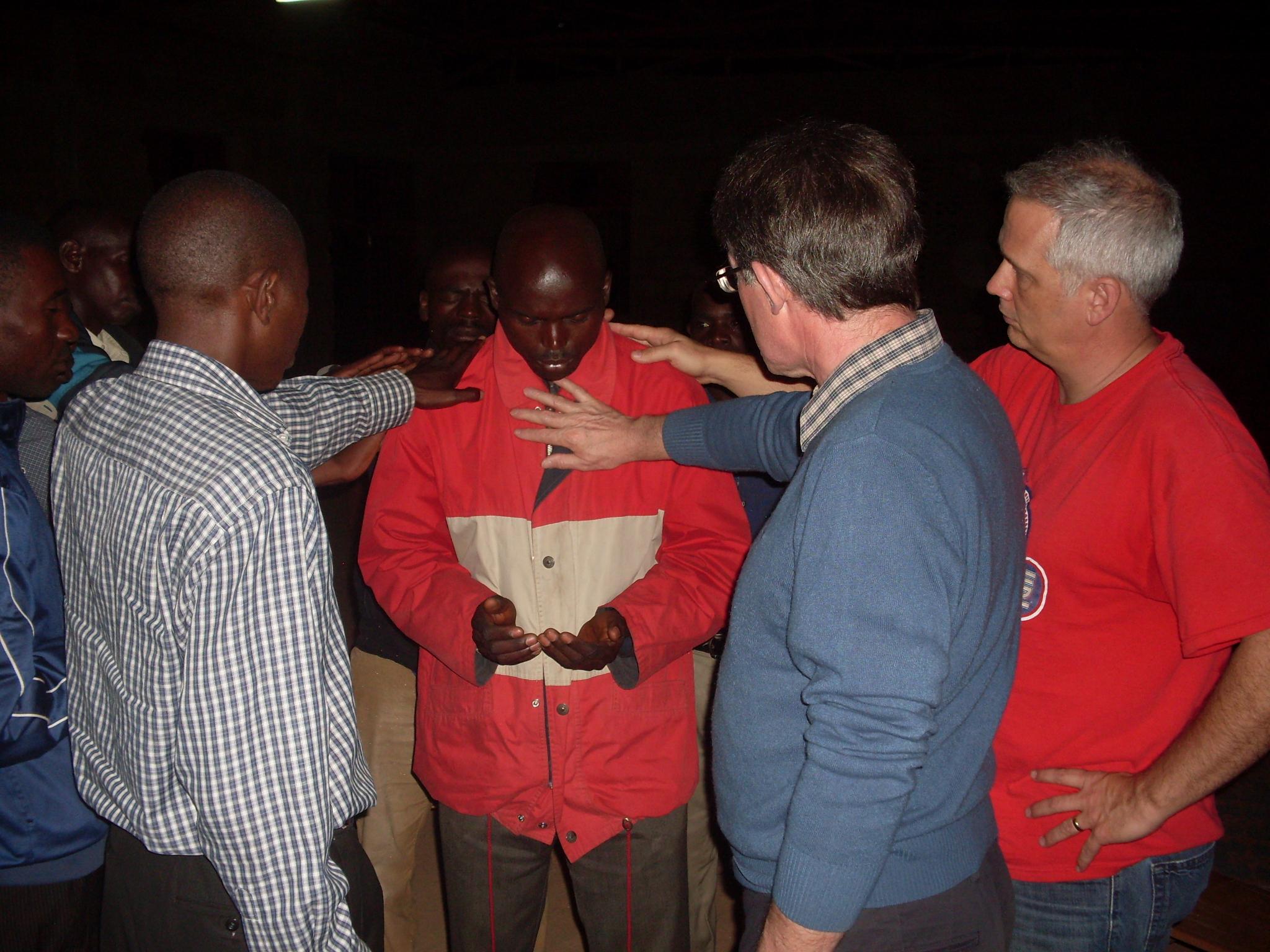 RWANDA - Group praying over a man.JPG