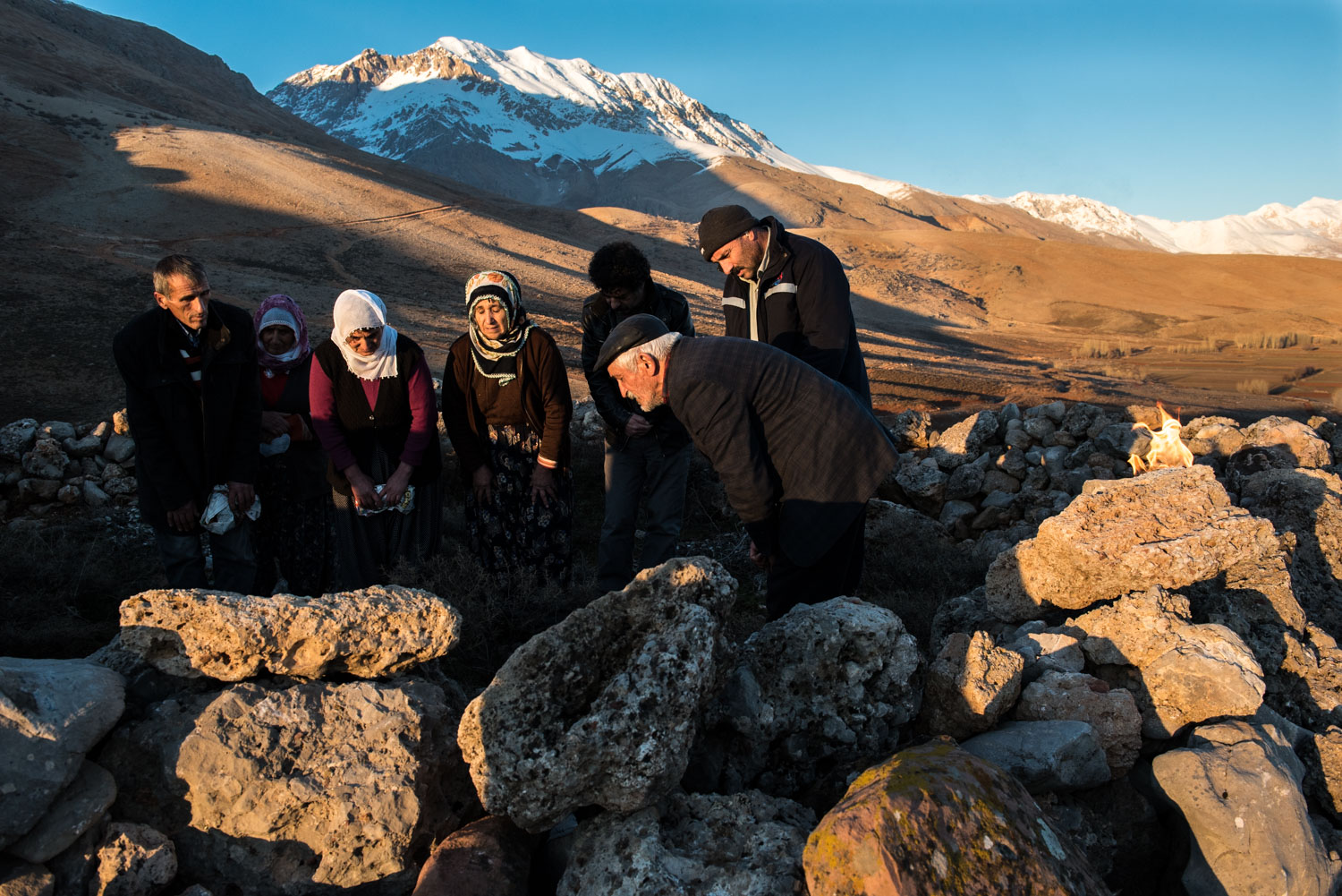 Men and women pray together in an outdoor ceremony on a sacred hill in the upper Munzur Valley.