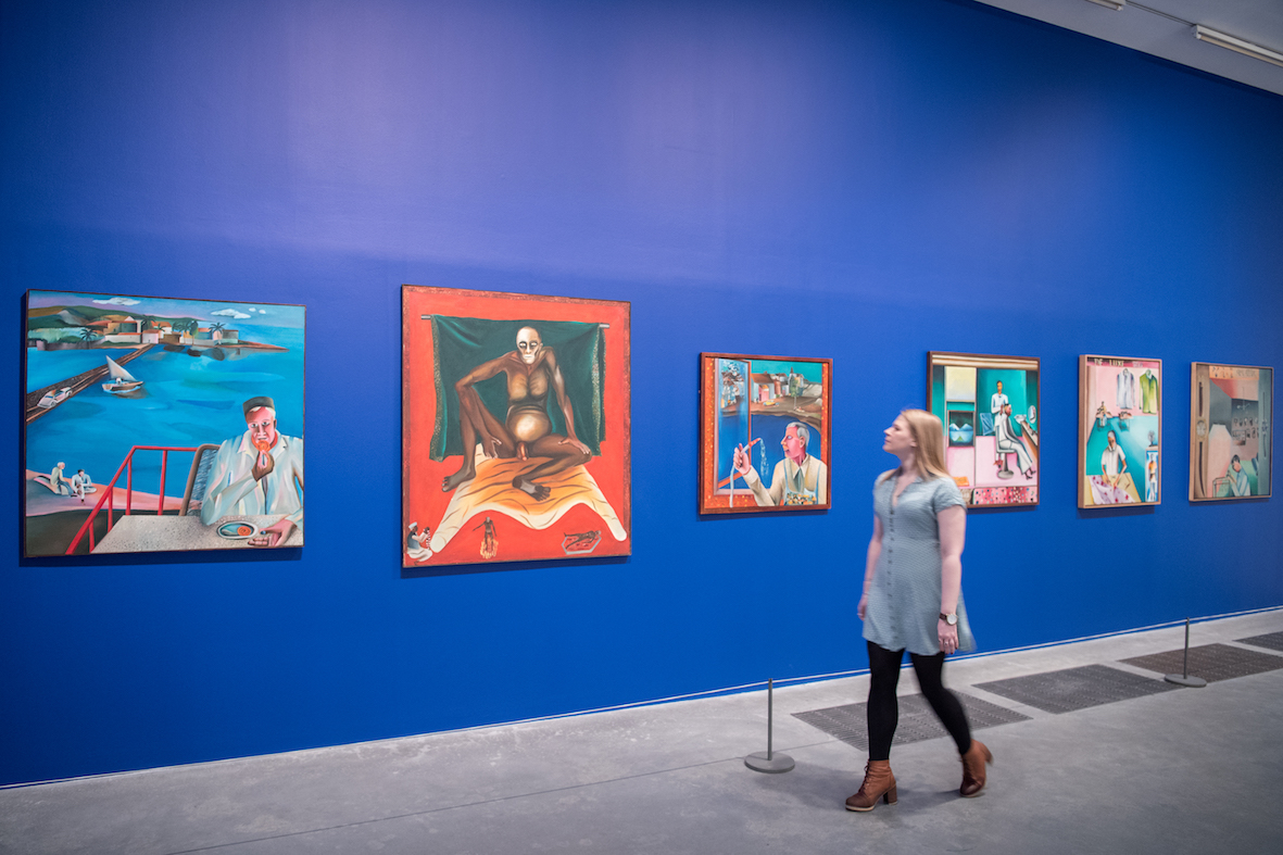 "Bhupen Khakhar, ""You Can't Please All"", Tate Modern, 2016, installation view. From left to right: 'Man Eating Jalebi', 1975, oil paint on canvas, 112 x 112 cm; 'Hathayogi', 1978, oil paint on canvas, 137 x 122 cm; 'Window Cleaner', 1982, oil paint on canvas, 91.5 x 91.5 cm; 'Barber's Shop', 1973, oil paint on canvas, 103.5 x 103.5 cm; 'The De-Luxe Tailors', 1972, oil paint on canvas, 106.7 x 83.8 cm; 'Janata Watch Repairing', 1972, oil paint on canvas, 107 x 107 cm. Image courtesy Tate Modern."