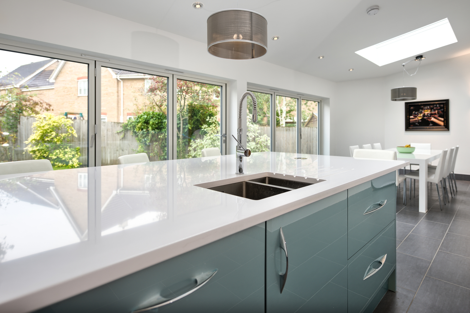 Island breakfast table with drawers of a lighting house extension by Harvey Norman Architects Cambridge