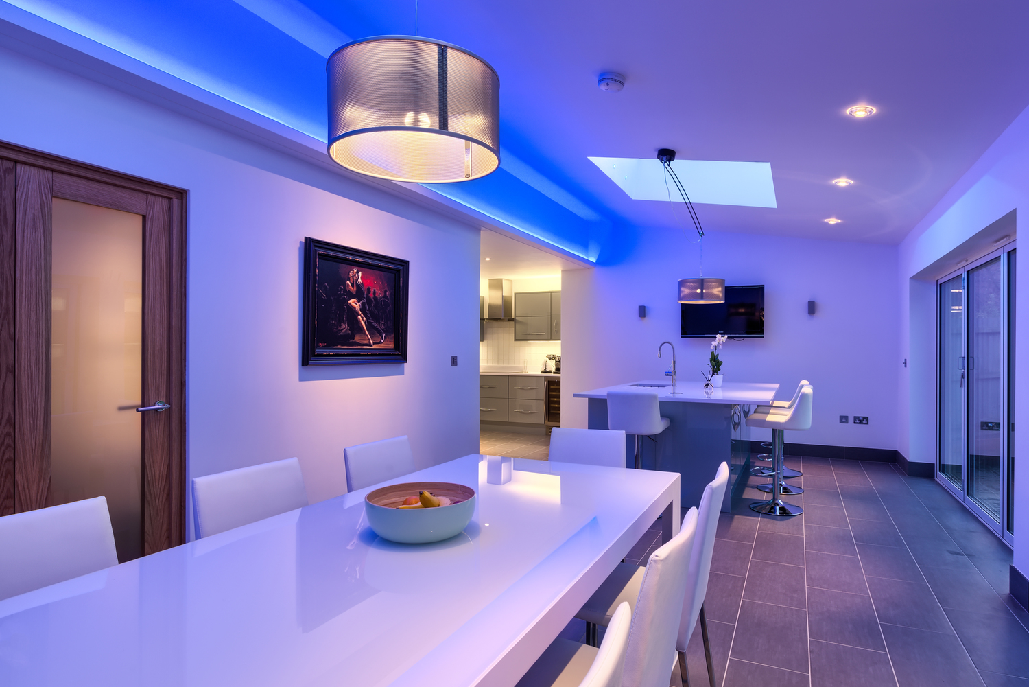 Breakfast bar blue light of a lighting house extension by Harvey Norman Architects Cambridge