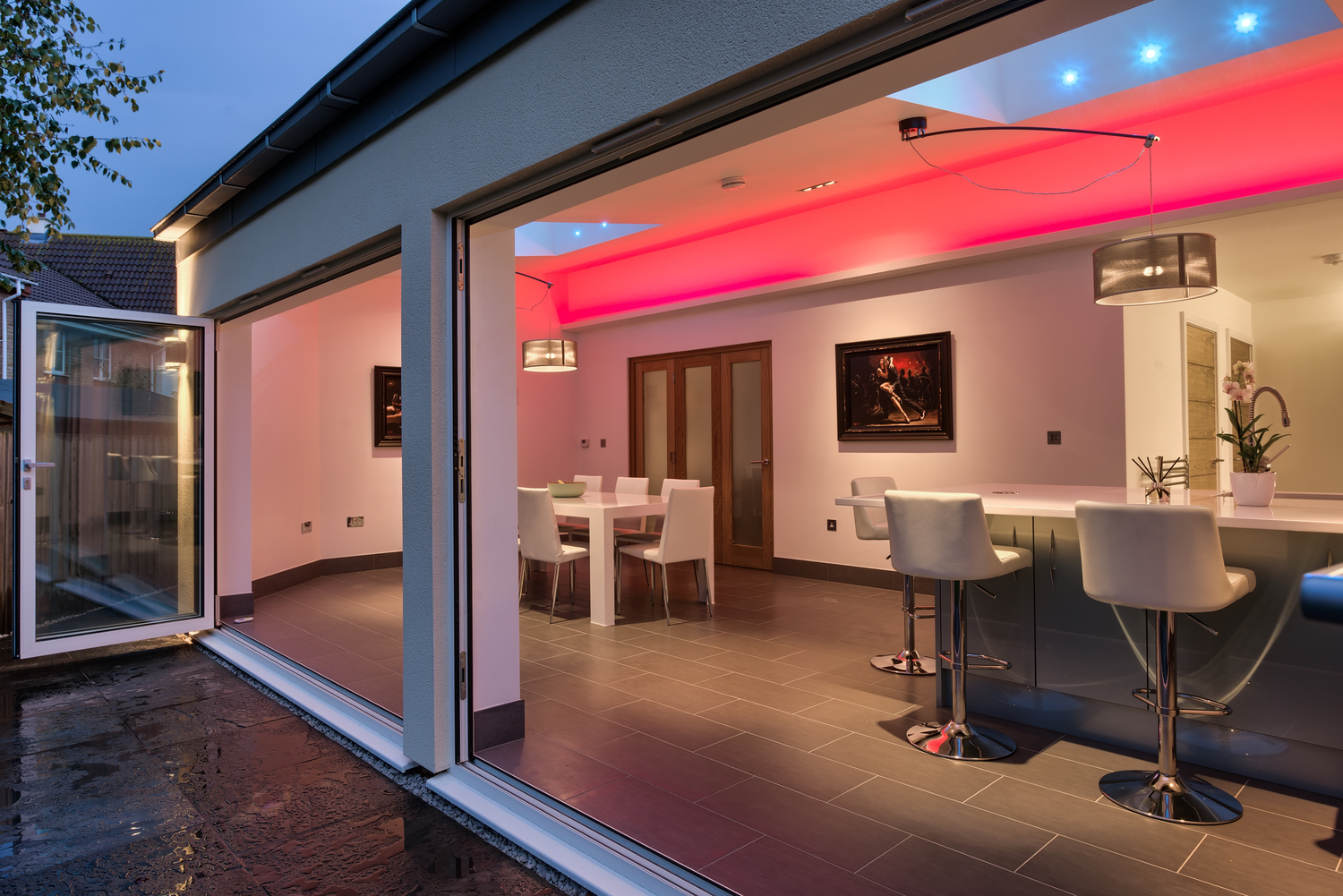 Sliding doors purple light of a lighting house extension by Harvey Norman Architects Cambridge