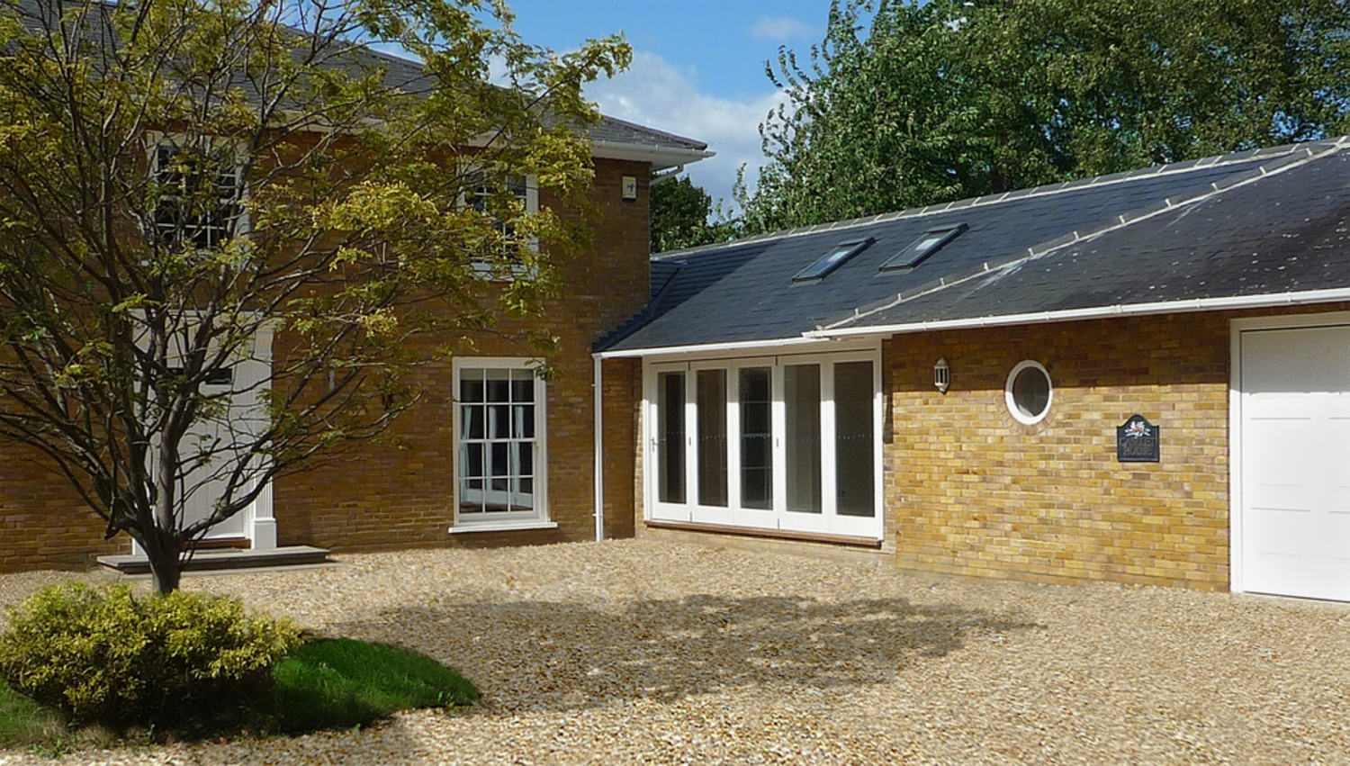 Driveway view of a house extension by Harvey Norman Architects Cambridge