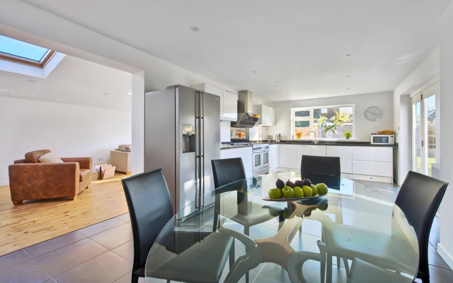Glass dining room table of a house extension by Harvey Norman Architects Cambridge