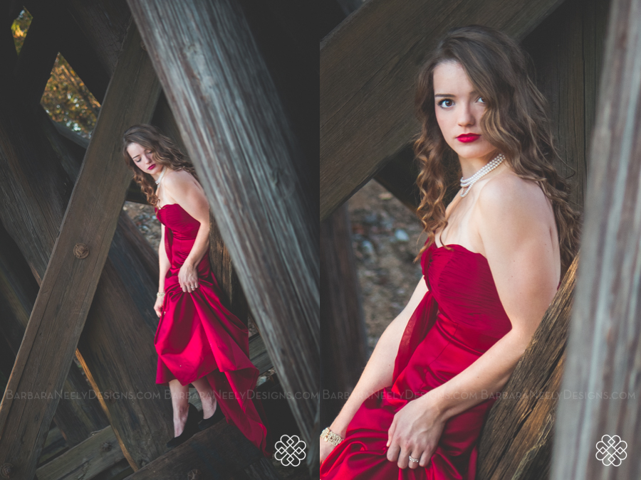 Very dramatic senior girl in red prom dress on railroad truss